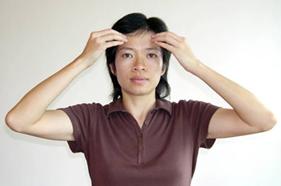 Das Bild zeigt eine Frau, die mit den Fingerspitzen beider Hände ihre Stirnbeinhöcker berührt.